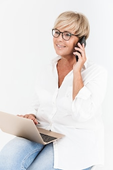 Portrait of adult woman wearing eyeglasses talking on smartphone while sitting with laptop computer isolated over white wall