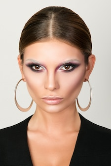 Portrait of adult woman with round earrings, catwalk beauty look