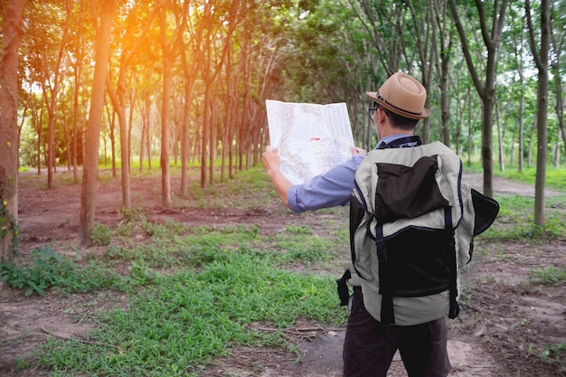 Portrait of adventure man with map and extreme explorer gear on forest with sunrise or sunset