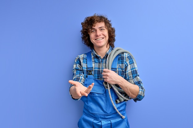 Portrait of affable plumber man with hose on shoulders ready to help clients