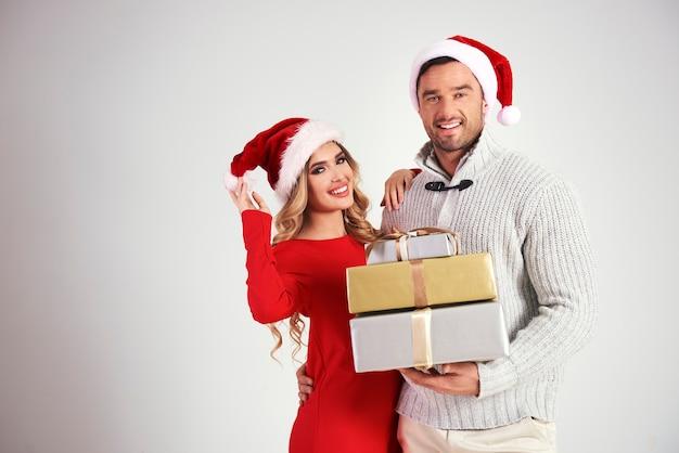 Ritratto di coppia affettuosa in possesso di una pila di regali di natale