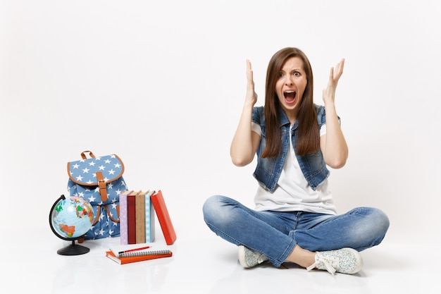 Ritratto di una studentessa arrabbiata e impaurita in abiti di jeans che urla allargando le mani seduta vicino al globo, zaino, libri scolastici isolati