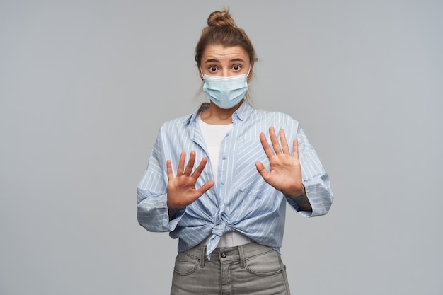 Portrait of afraid girl with blond hair gathered in bun. wearing striped shirt and protective face mask. push her hands away, keep distance. looking at the camera, isolated over grey wall