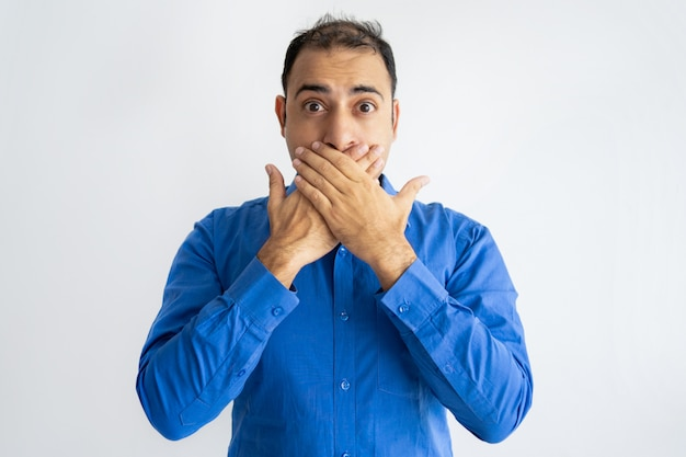 Portrait of afraid mid adult businessman covering mouth