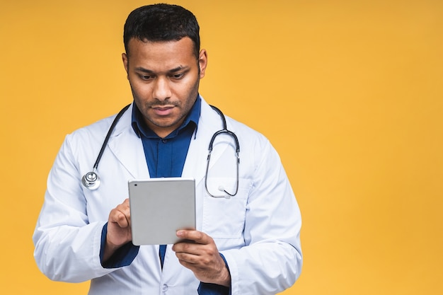 Portrait of african american black indian doctor man using a tablet computer isolated over yellow background.