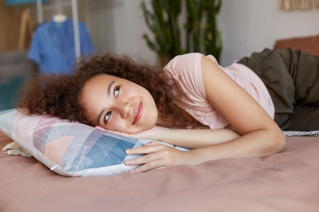 Портрет афро-американской мечтательной дамы, лежащей на кровати, наслаждается солнечным утром дома, широко улыбаясь и смотрит вверх.