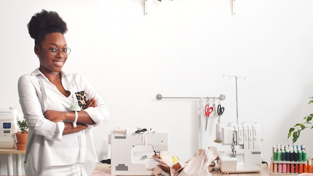 Portrait of an african-american fashion designer working in a studio, smiling fashion designer looks at the camera