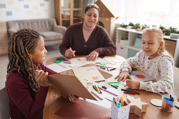 Portrait of african-american girl showing picture while enjoying art and craft class in school, copy space