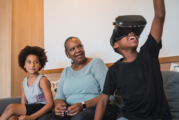 Portrait of african american grandmother and grandchildren playing together with vr glasses at home. family and technology concept.