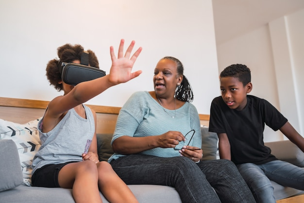 Portrait of african american grandmother and grandchildren playing together with vr glasses at home