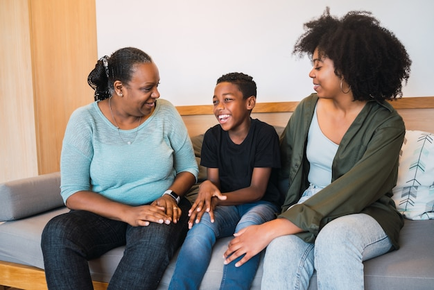 Portrait of african american grandmother, mother and son spending good time together at home