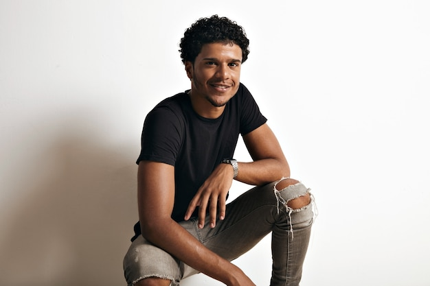 Portrait of an african american man in a black cotton t-shirt and torn jeans sitting at the wall of a white