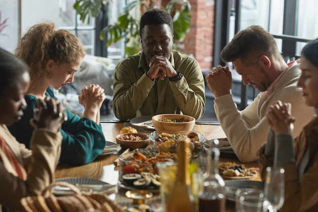 Portrait of african-american man praying with eyes closed while sitting at dinner table during thanksgiving celebration with friends and family,