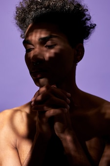 Portrait of african american man in shadow with pray pose transgender male stand with eyes closed