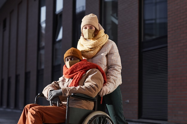 Portrait of african american man using wheelchair and wearing mask in urban city with young woman assisting, copy space