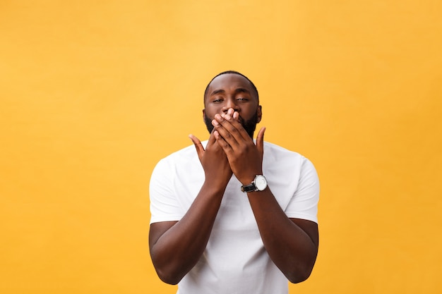 Portrait of african american man with hands raised in shock and disbelief. isolated over yellow background.