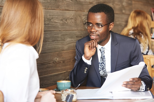 Portrait of african american recruiter in formal wear interviewing redhead female applicant