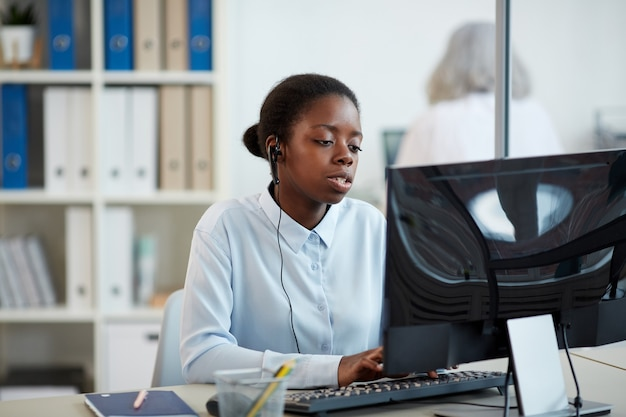 Portrait of african-american woman wearing headset while working as call center operator in office interior