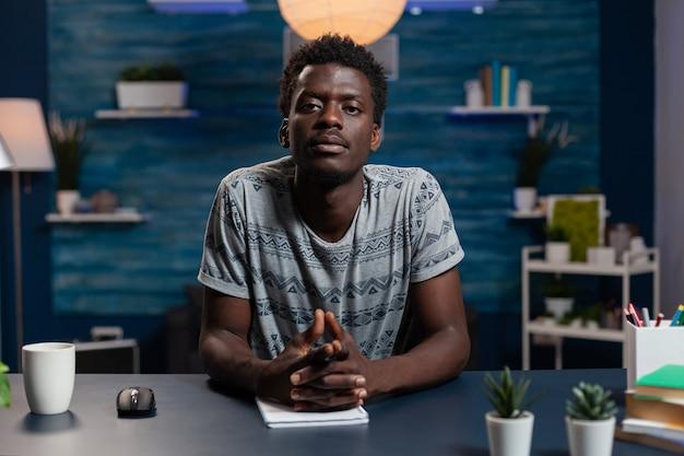 Ritratto di giovane impiegato afroamericano che ha riunione di videochiamata online