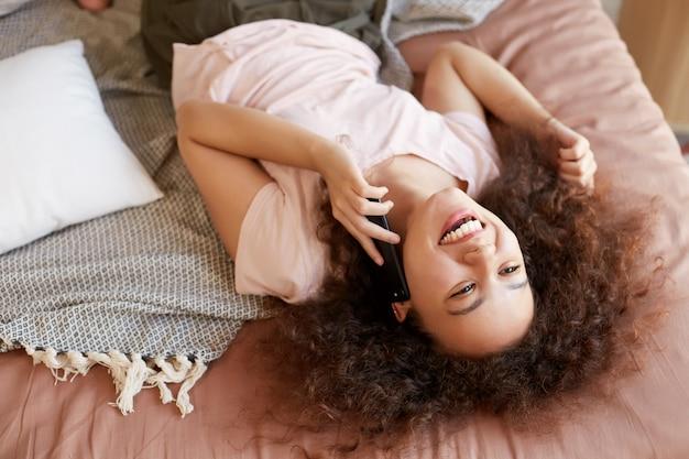 Ritratto di giovane donna afroamericana sdraiata sul letto nella sua stanza e parla al telefono, ampiamente sorridente e godersi la giornata a casa.