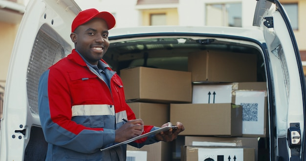 Portrait of the african american young male worker of shipping company standing at the van with boxes and writing the document, then smiling to the camera. outdoors.
