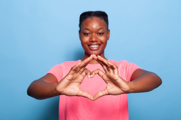 Portrait of african american young woman making heart symbol with fingers