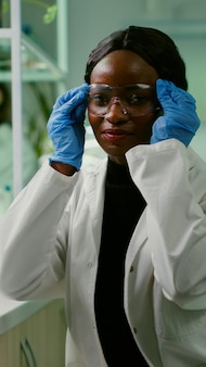 Portrait of african biologist in white coat looking into camera working in microbiology laboratory