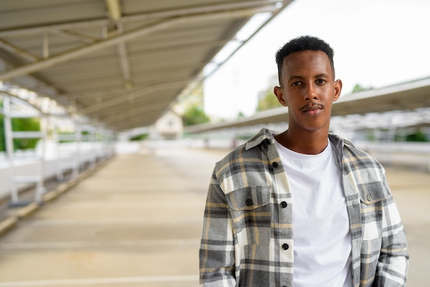 Portrait of african black man outdoors in city during summer horizontal shot Premium Photo