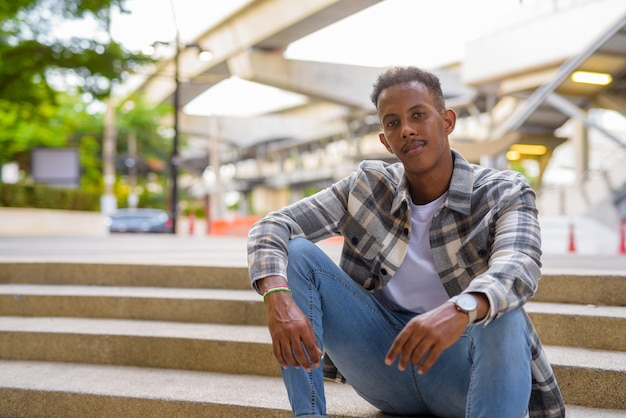 Portrait of african black man outdoors in city during summer horizontal shot