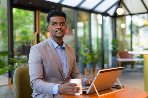 Portrait of african businessman at coffee shop using laptop computer and holding paper coffee cup