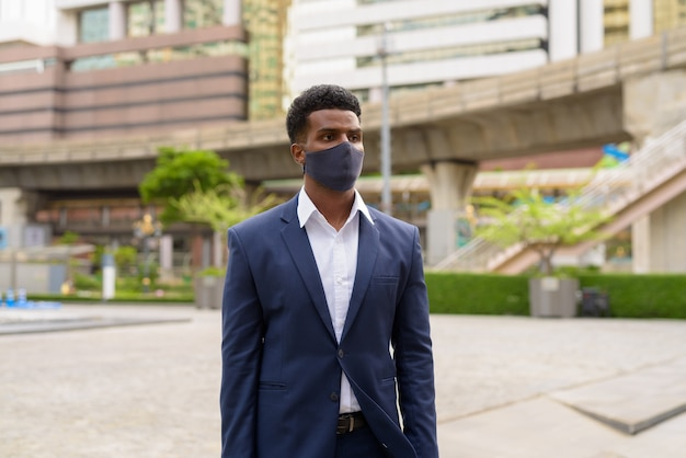 Portrait of african businessman thinking and wearing face mask outdoors, horizontal shot