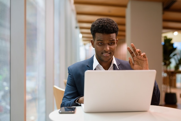 Portrait of african businessman using laptop computer in coffee shop while waving and having video call, horizontal shot