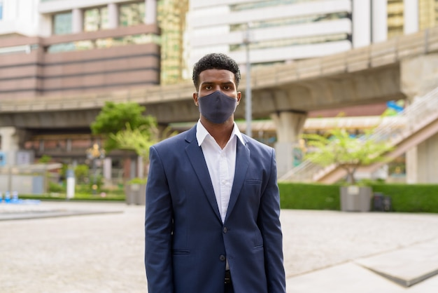 Portrait of african businessman wearing face mask outdoors in city, horizontal shot