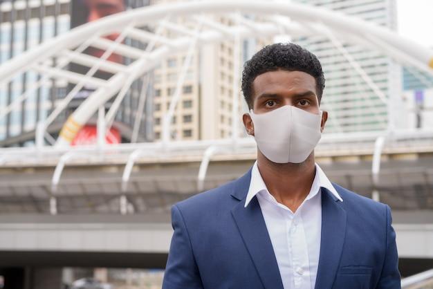 Portrait of african businessman wearing face mask outdoors, horizontal shot