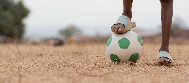 サッカーボールの肖像画アフリカの子をクローズアップ