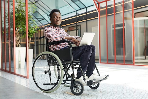 Portrait of african disabled man sitting in wheelchair and looking while working on laptop