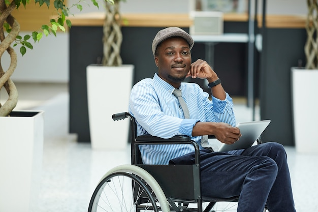 Portrait of african disabled man sitting in wheelchair and using digital tablet