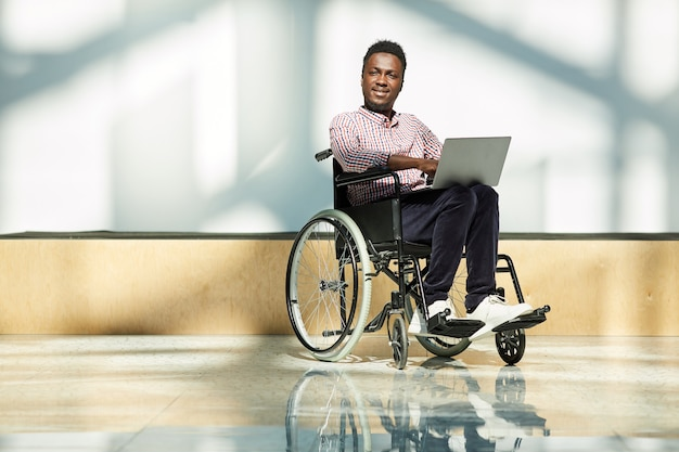 Portrait of african disabled man in wheelchair looking while working online on laptop computer