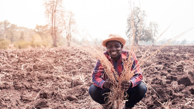 Portrait of african farmer man standing at the dry field