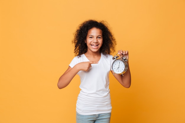 Portrait of a african girl pointing finger at alarm clock