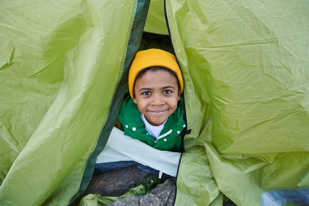 Portrait of african little boy sitting in tent and