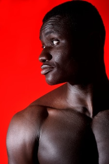 Portrait of an african man shirtless on red background