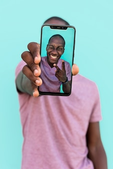 Portrait of an african man showing a selfie on his phone