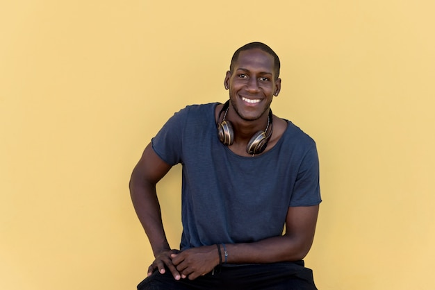 Portrait of an african man with headphones laughing on colorful wall