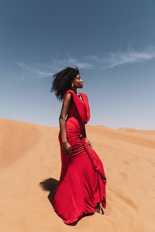 A portrait of a african woman in a dune with a red dress in the sahara desert