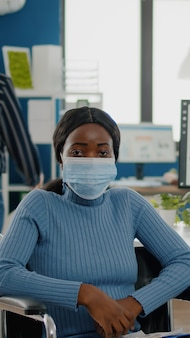 Portrait of african woman with protection face mask looking at camera