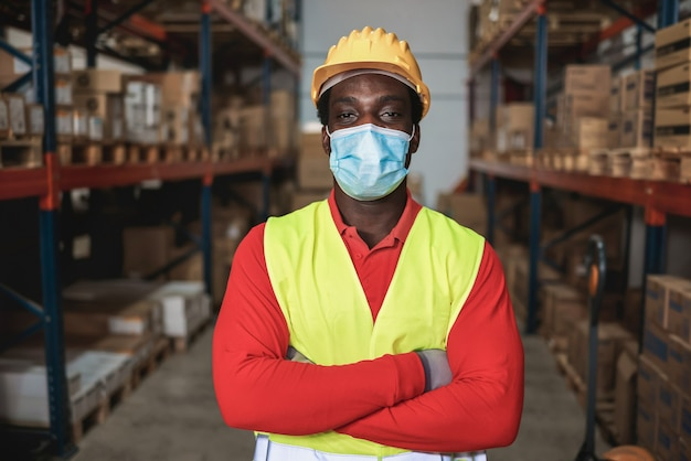 Portrait of african worker man inside warehouse while wearing safety mask - focus on man eyes