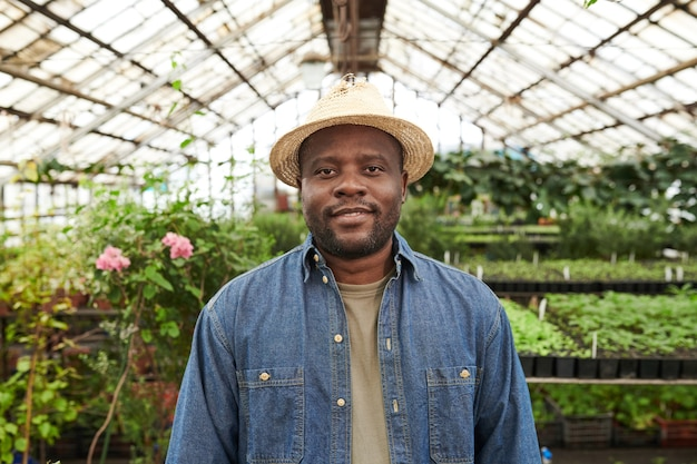 Portrait of african young farmer in hat looking at camera while working in the garden