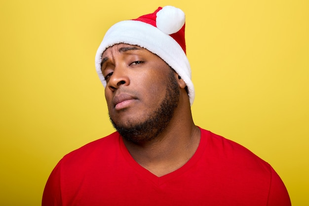 Portrait of an africanamerican guy in a christmas hat looking haughtily straight into the camera