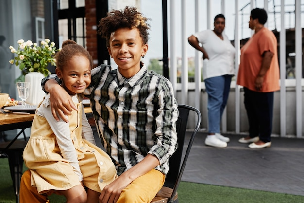Portrait of africanamerican teenage boy posing with little sister during family gathering outdoors c...